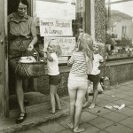 Nainen astuu ulos kaupan ovesta ostoskori kädessään. Kolme kesäasuista lasta pyörii naisen ympärillä. Yksi lapsista osoittaa suoraan kameraan.