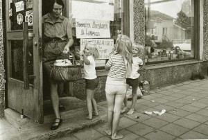 Nainen tulee ostoskoria kantaen ulos kaupan ovesta. Ympärillä pyörii kolme lasta.