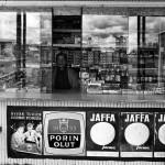 Myyjä katsoo kioskin sisältä kohti kameraa.